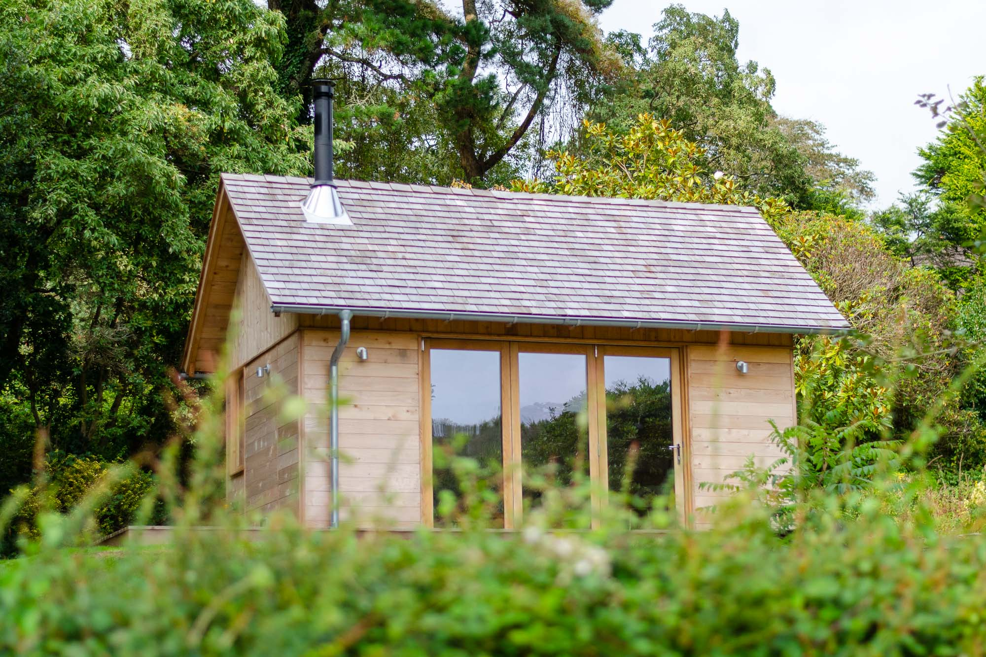 wooden office cabin with cedar shingle roof and bifold oak doors and veranda in garden