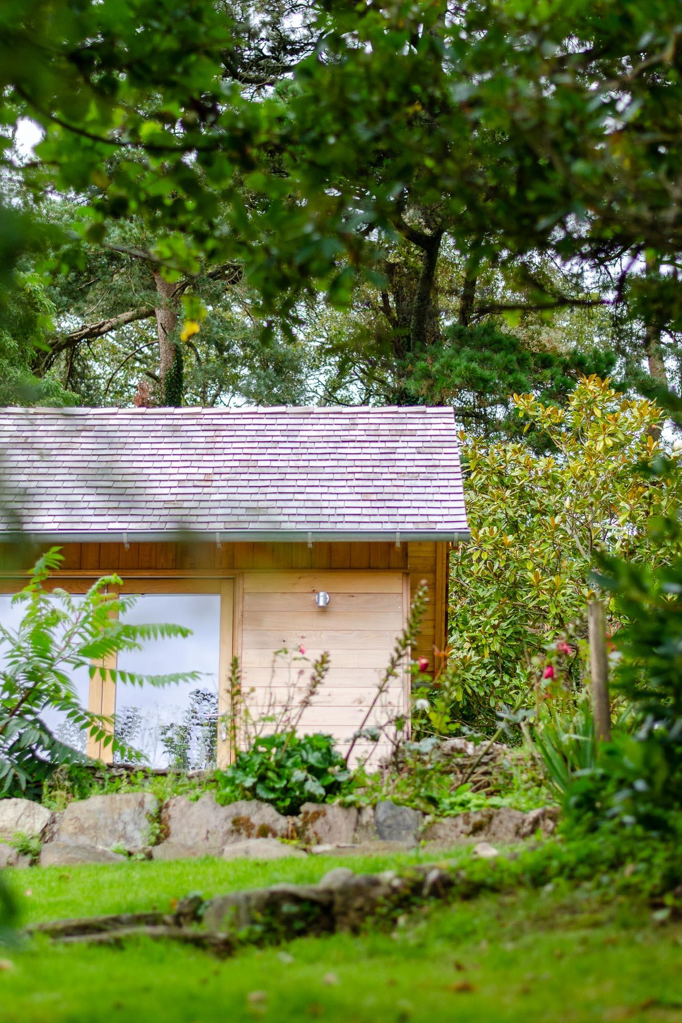 wooden office cabin with cedar shingle roof and bifold oak doors and veranda in garden over looking valley