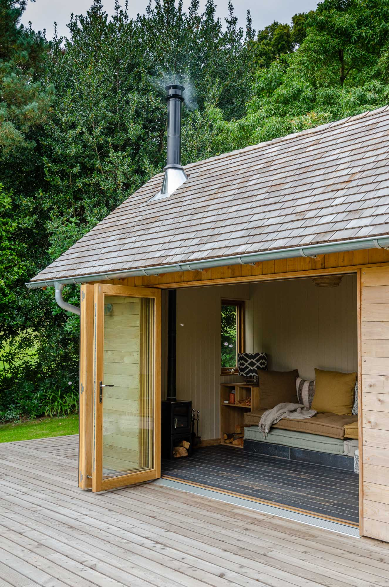 wooden office cabin with cedar shingle roof and bifold oak doors and veranda in garden over looking valley