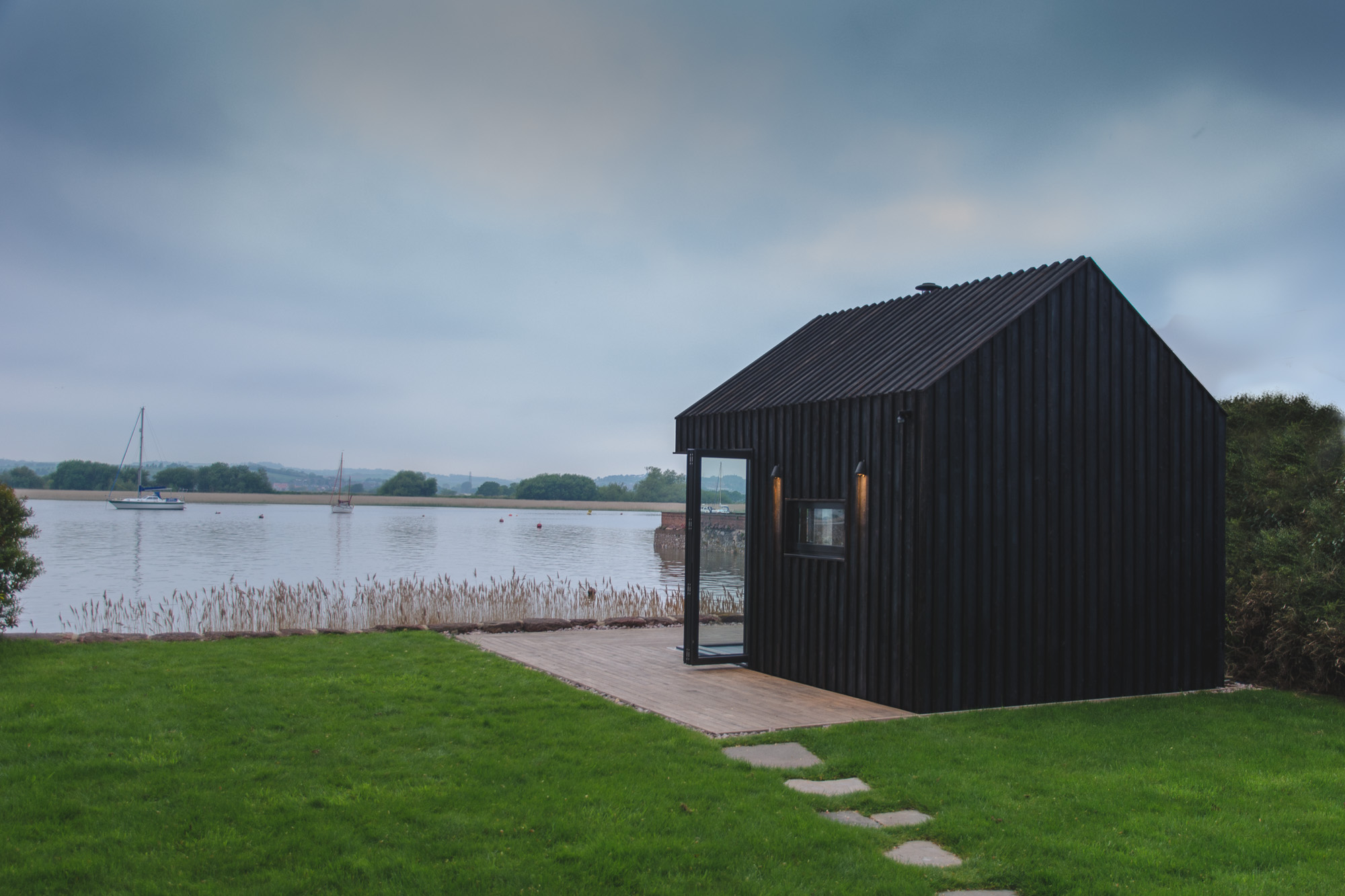 wooden cabin with oak panelling and wood burning stove overlooking an estuary in a garden