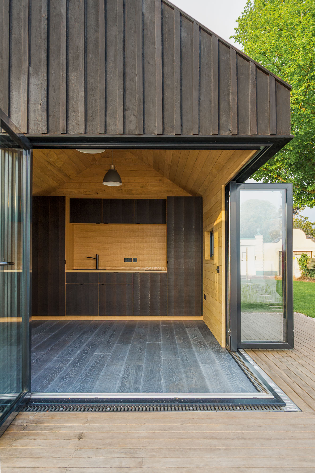 wooden cabin with shou sugi ban cladding and built in kitchen with bi-fold doors open