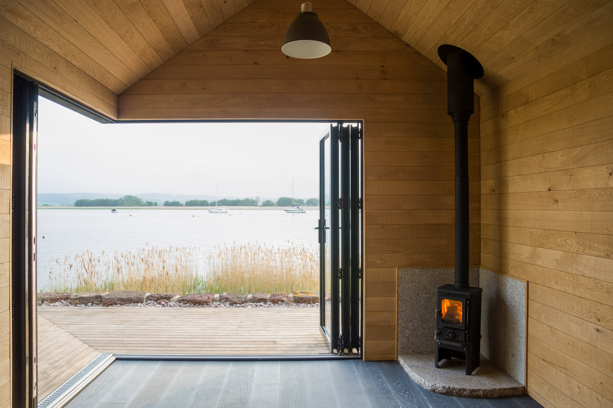wooden cabin with oak panelling and wood burning stove overlooking an estuary
