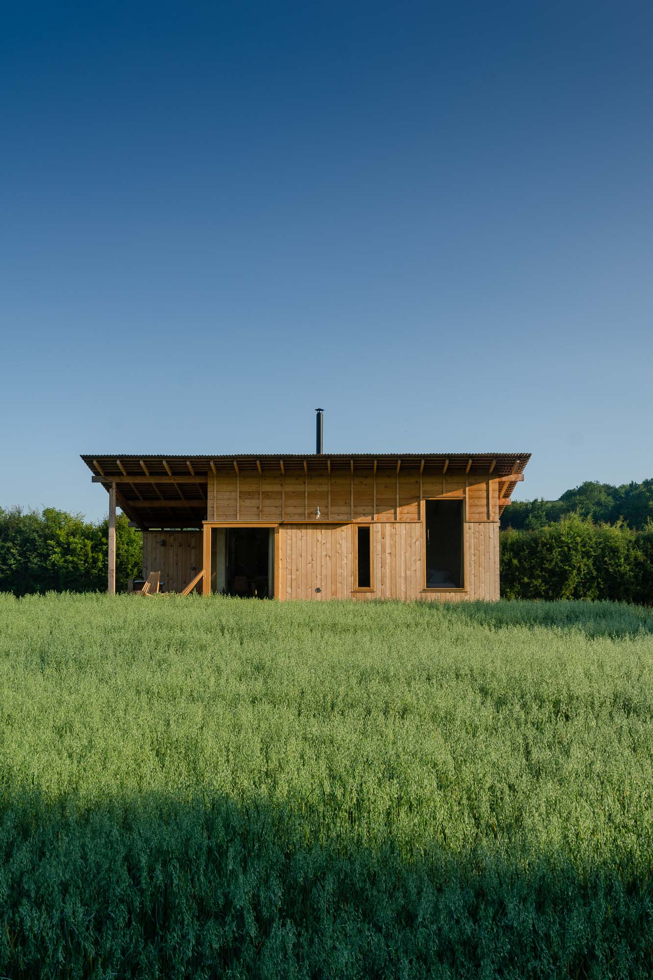 off-grid bespoke cedar cabin with covered veranda, outdoor copper in corn field