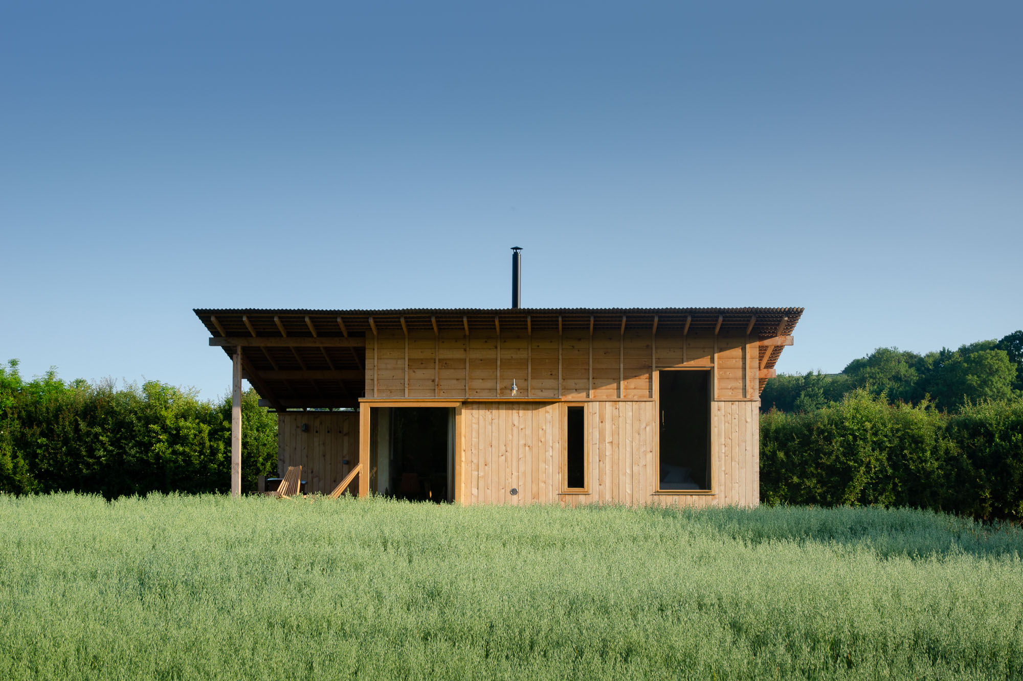 off-grid bespoke cedar cabin with covered veranda, outdoor copper and bench overlooking nature landscape