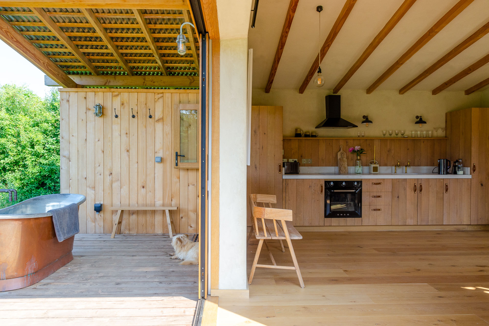 off-grid bespoke cedar cabin with covered veranda, outdoor copper bath, oak and concrete kitchen