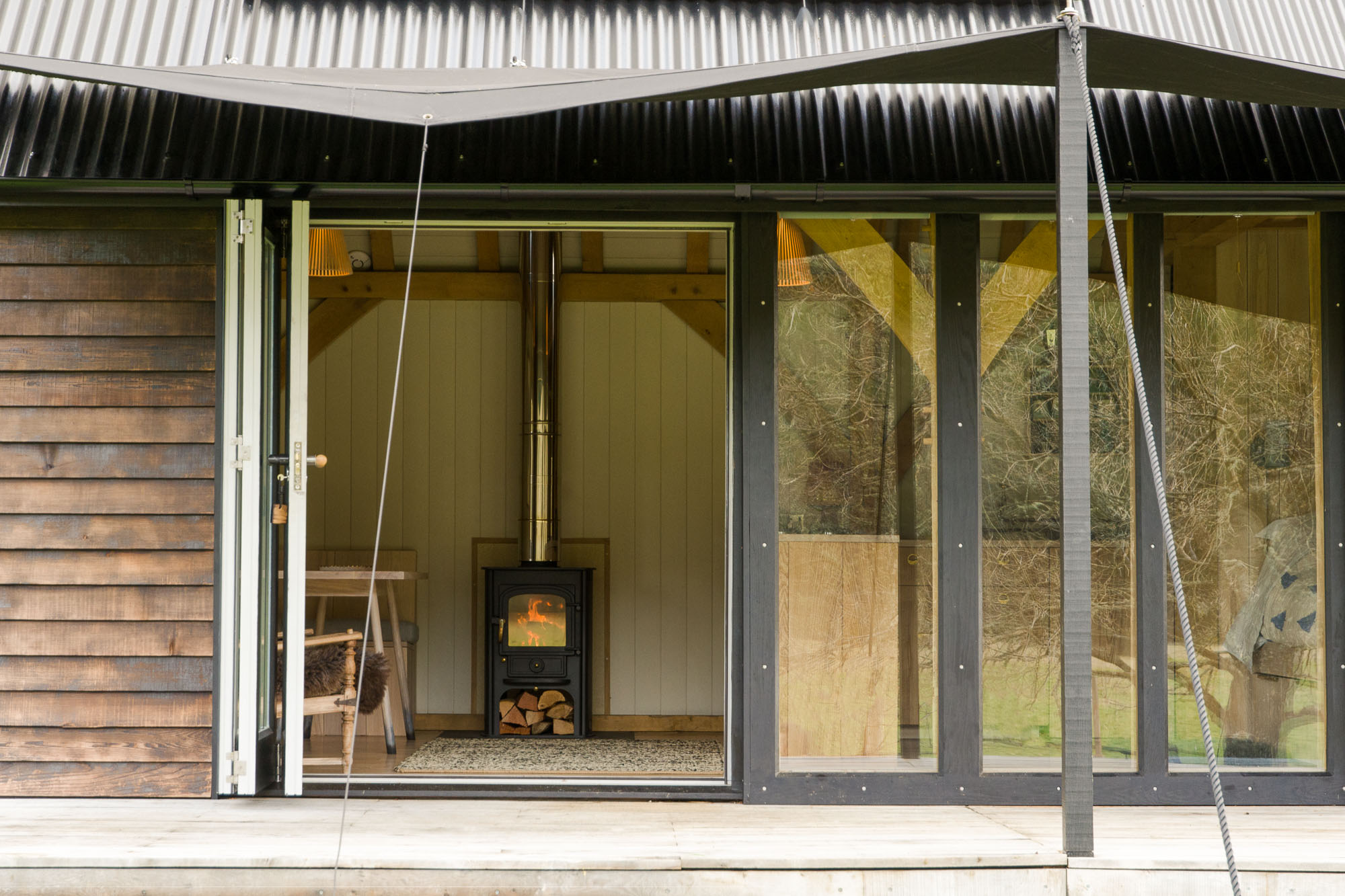 off grid wooden cabin with black shou sugi ban cladding and canvas covered veranda, wood burning stove and oak interior