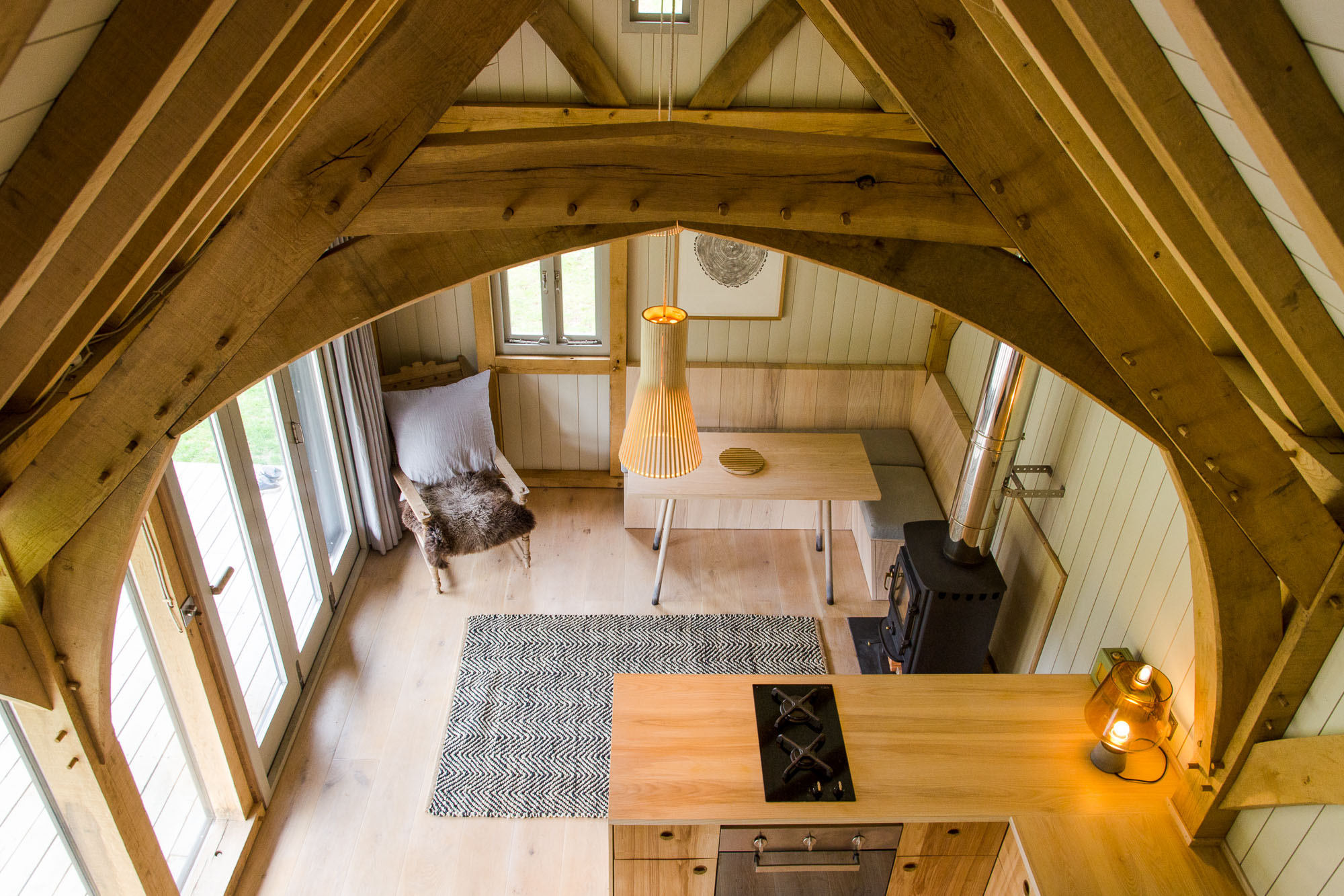 off grid wooden oak framed cabin interior with built on kitchen and living area with wood burning stove