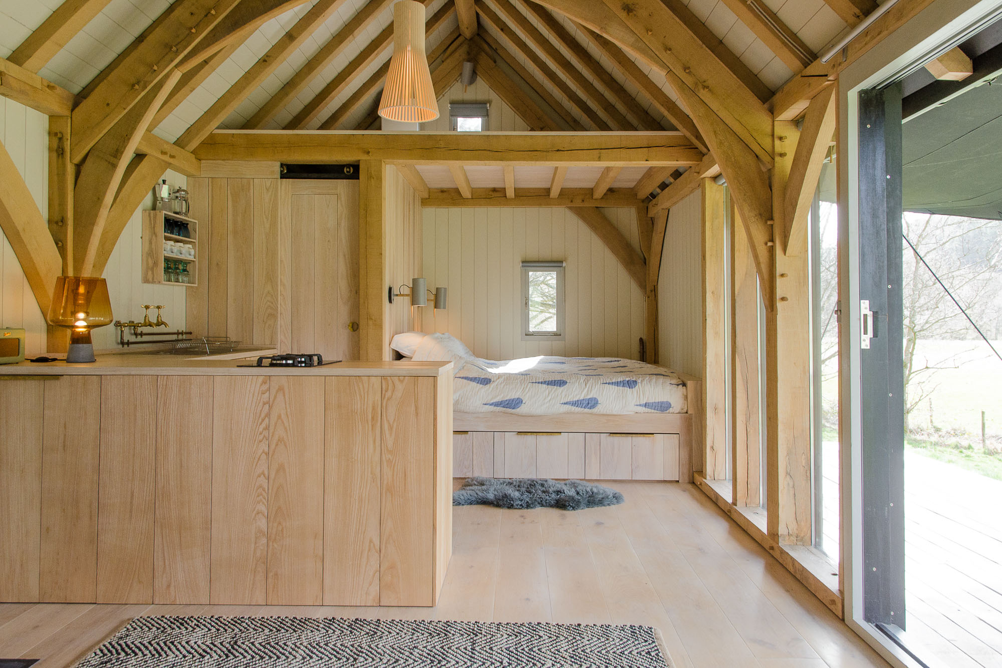 off grid wooden oak framed cabin interior with built on kitchen, bedroom and marble bathroom with oak floor and walls