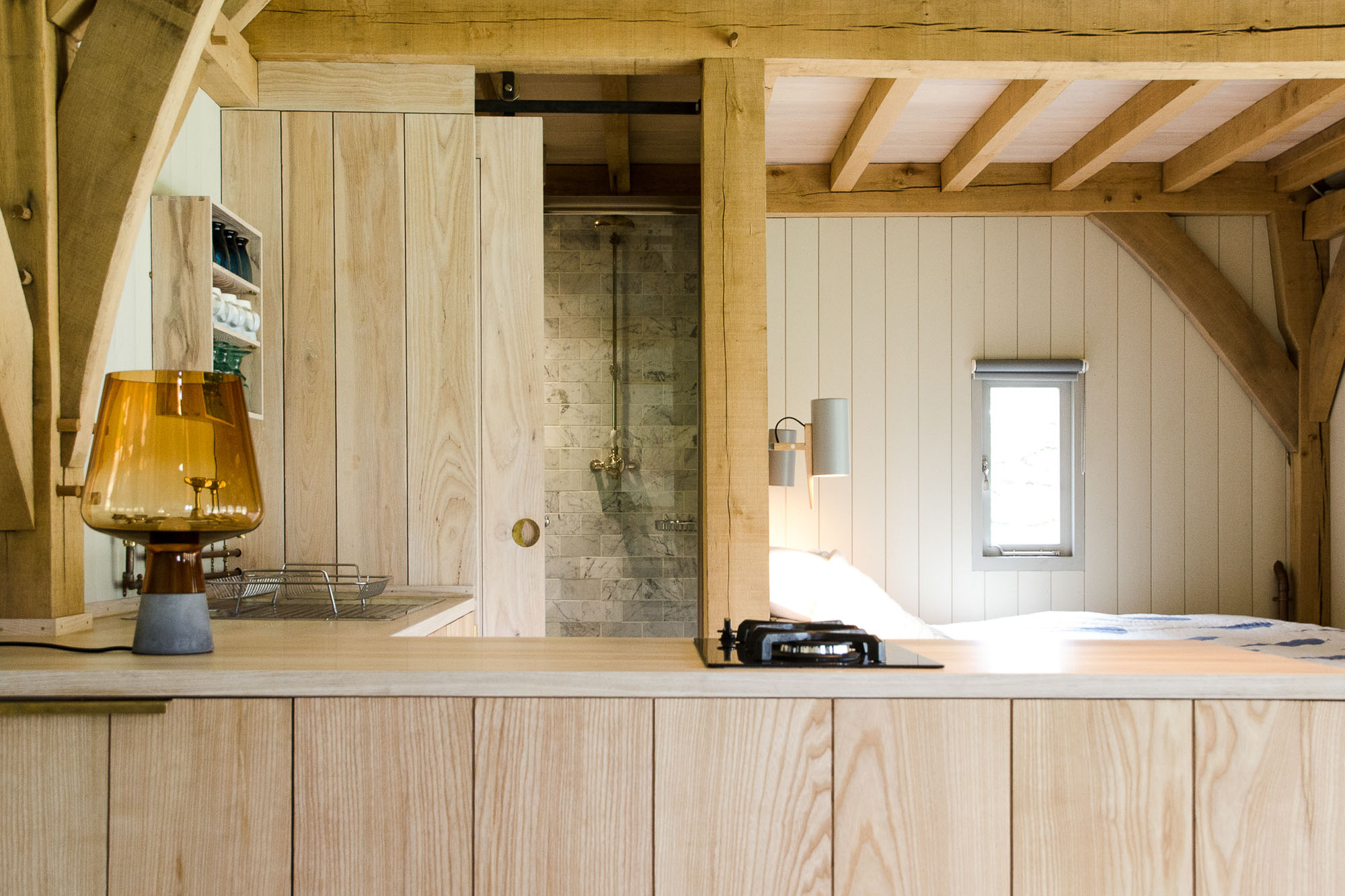 off grid wooden oak framed cabin interior with built on kitchen and marble bathroom