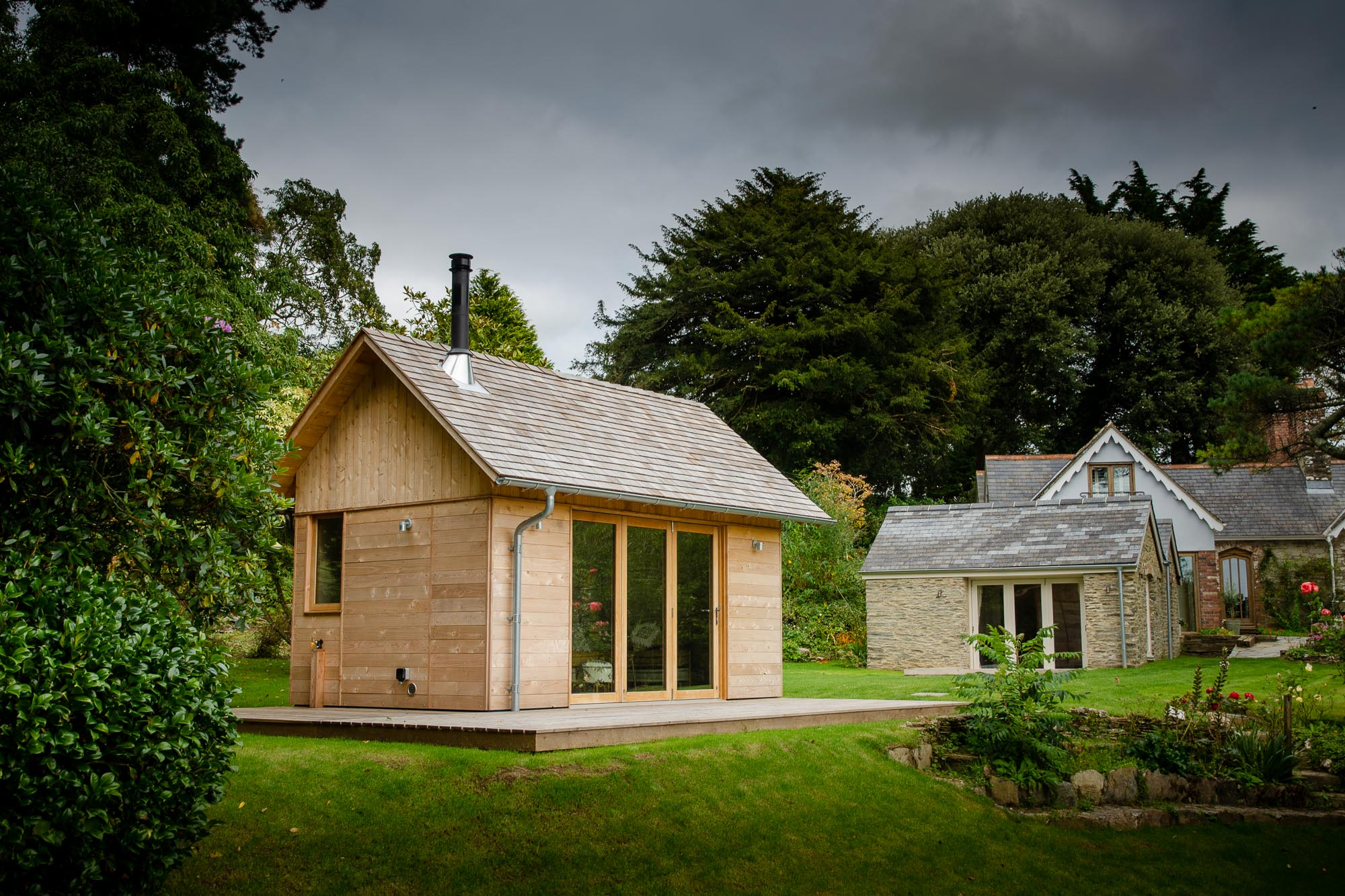 wooden cedar wood cabin with cedar shingle roof and bifold oak doors and veranda