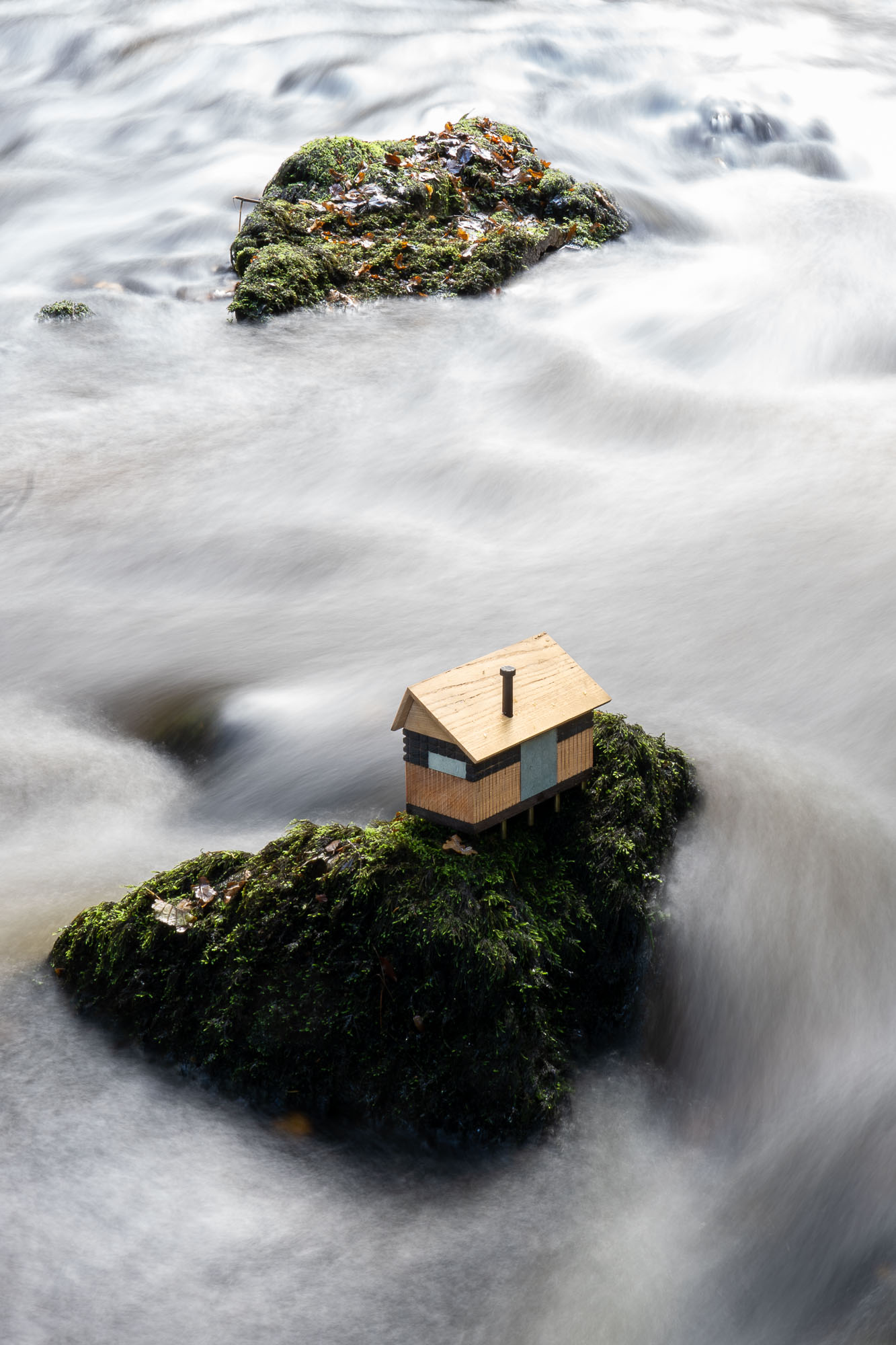 cabin model on a rock in a dartmoor river