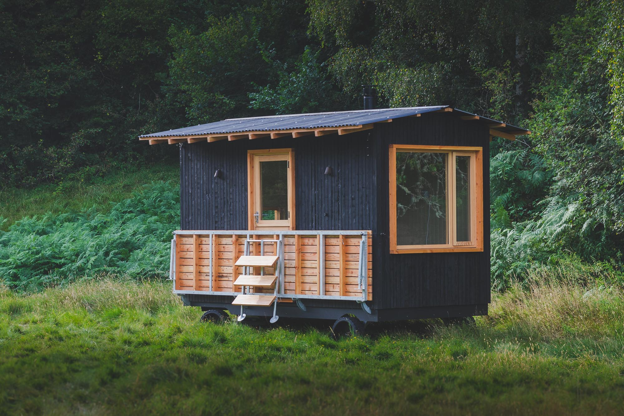 off grid tiny wooden mobile nomad cabin with black cladding and corrugated roof