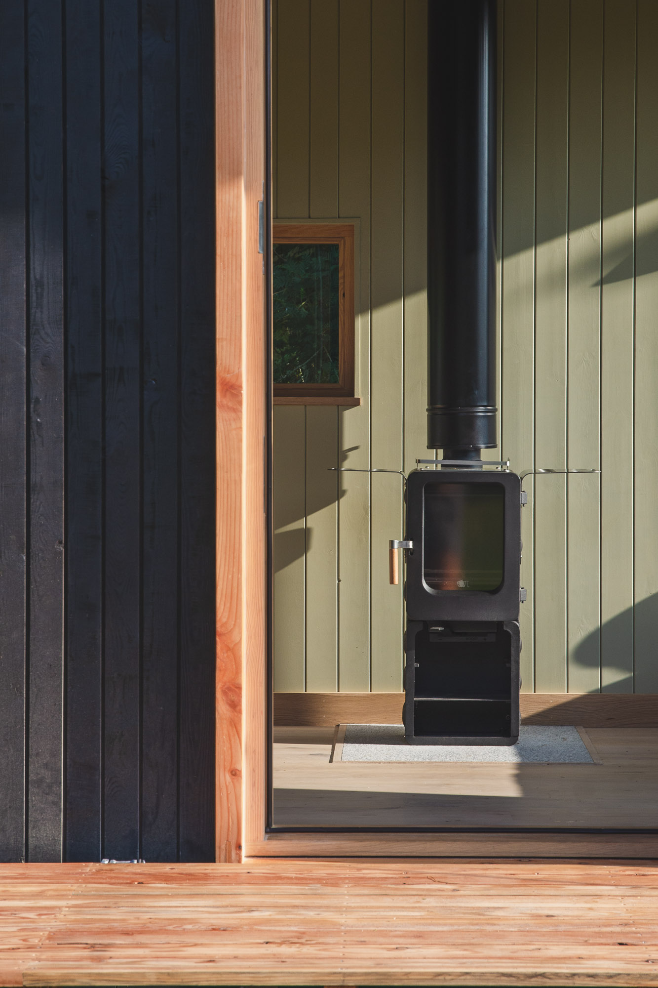 off grid tiny wooden nomad cabin with black cladding and tongue and groove panelling with wood burning stove and stable door