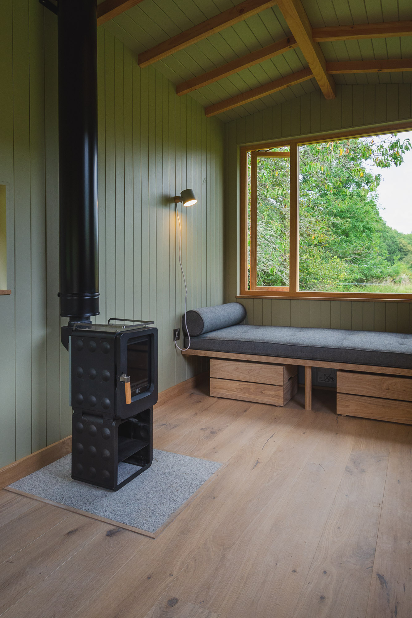 off grid tiny wooden nomad cabin with ash daybed and wood burning stove, engineered oak floor and large windows