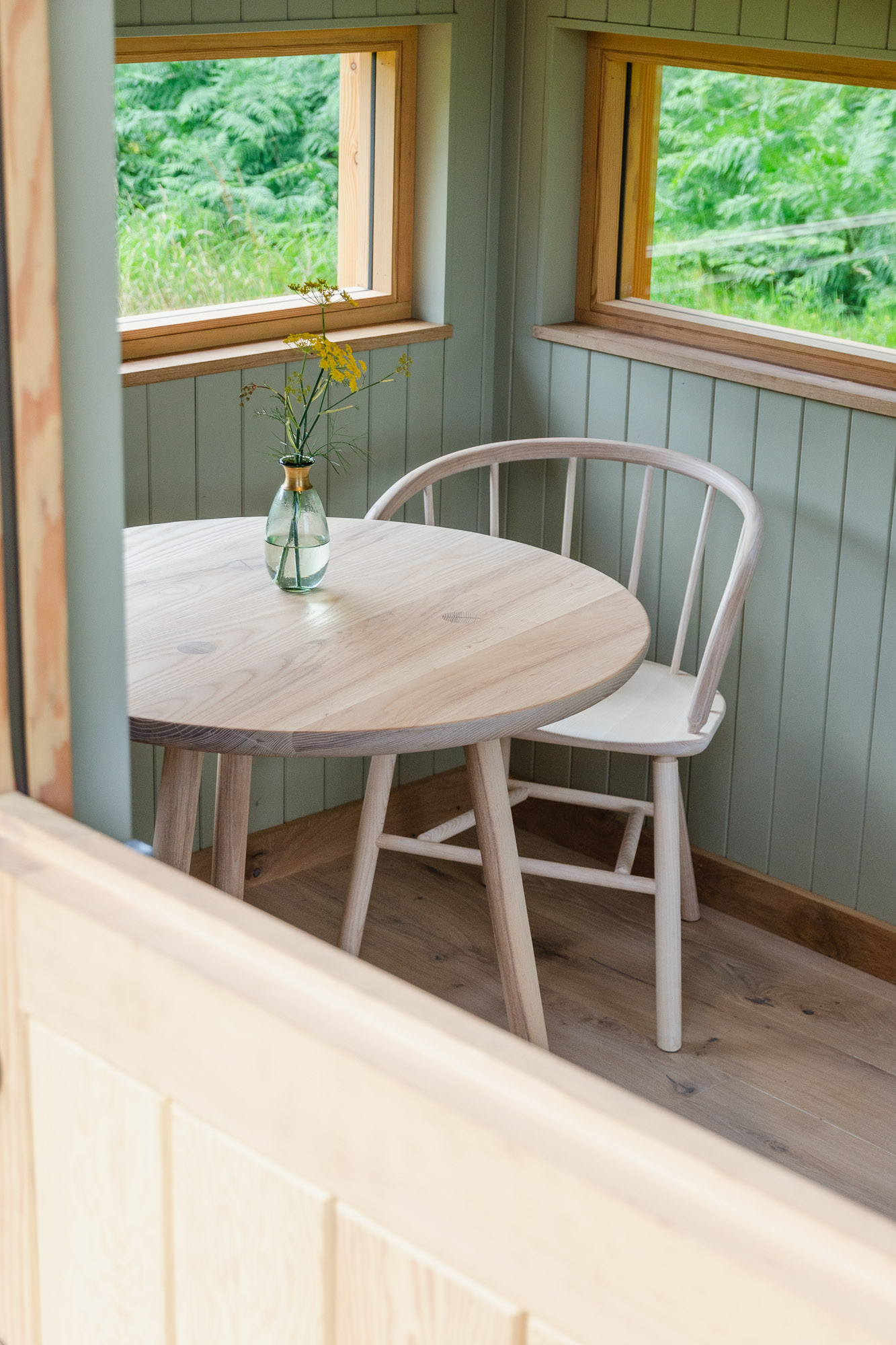 off grid tiny wooden nomad cabin office with ash table and chairs looking of natural landscape