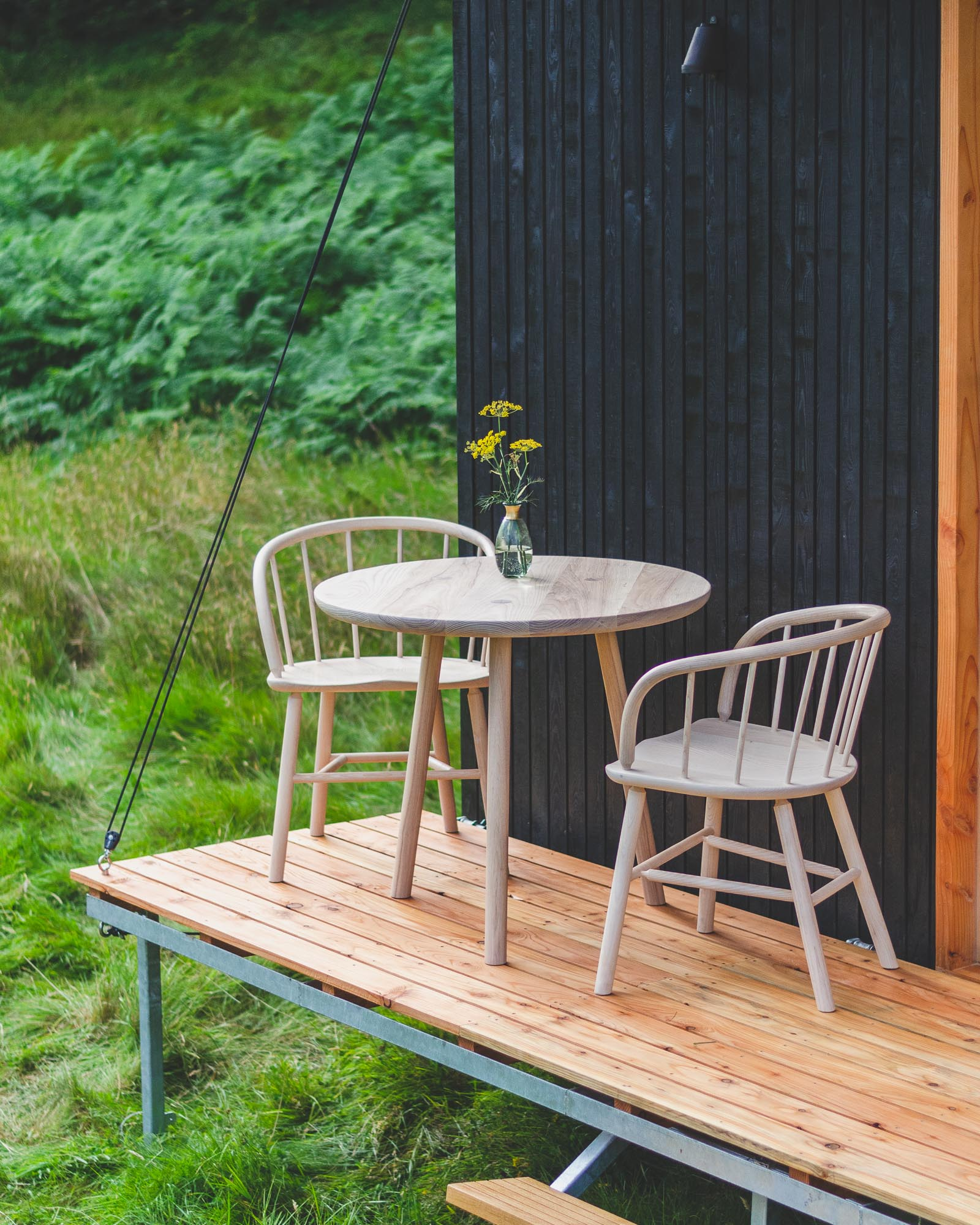 off grid tiny wooden nomad cabin office with black cladding, outdoor chairs and table on wooden deck