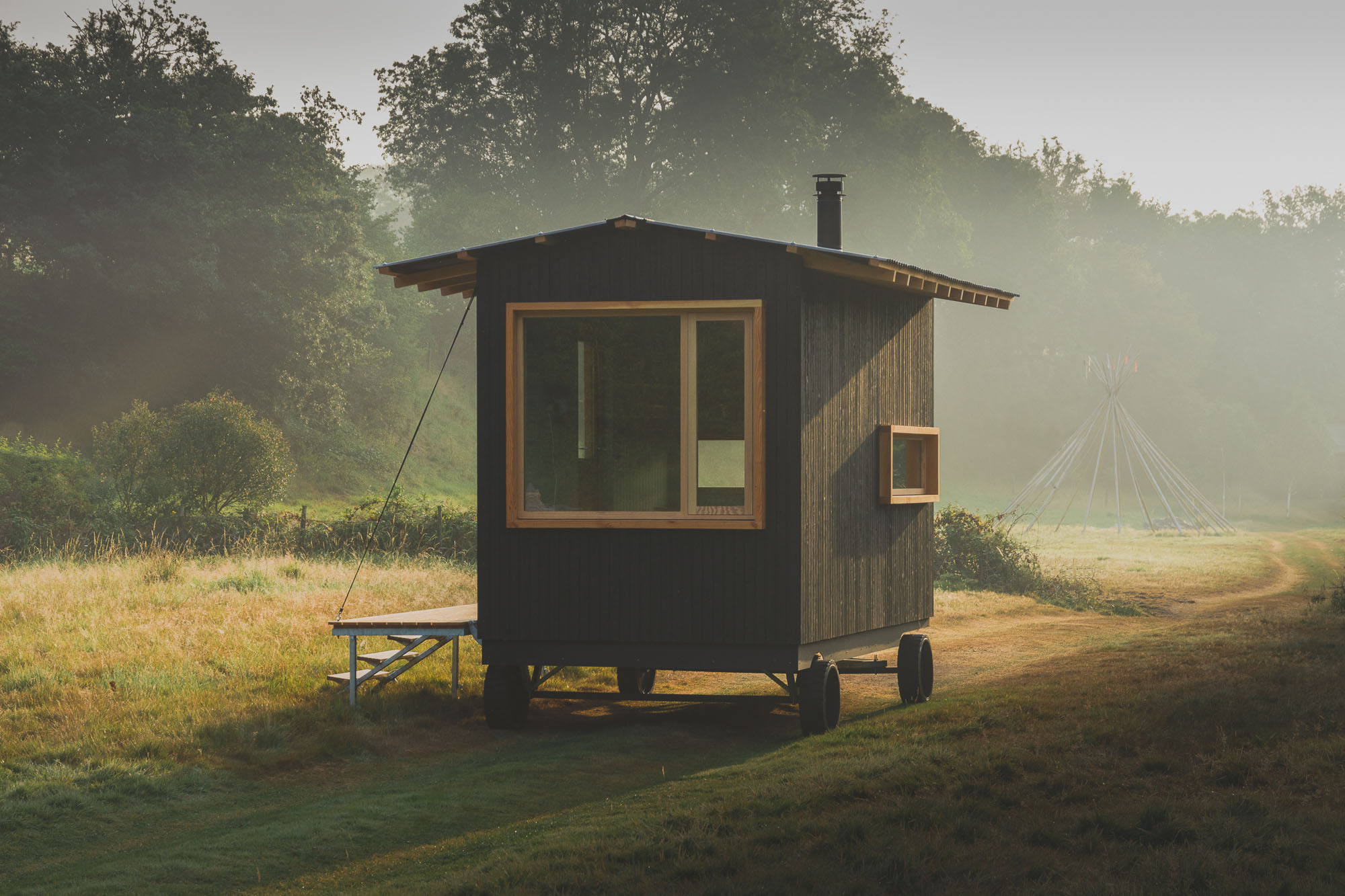 off grid tiny wooden nomad cabin with black cladding in a sunny field with outdoor deck and seating