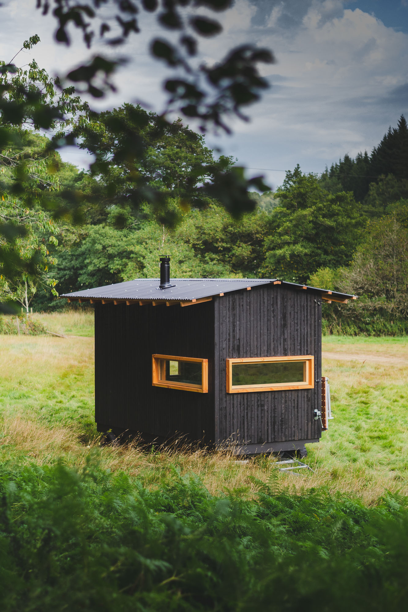 off grid tiny wooden nomad cabin with black cladding in a sunny field
