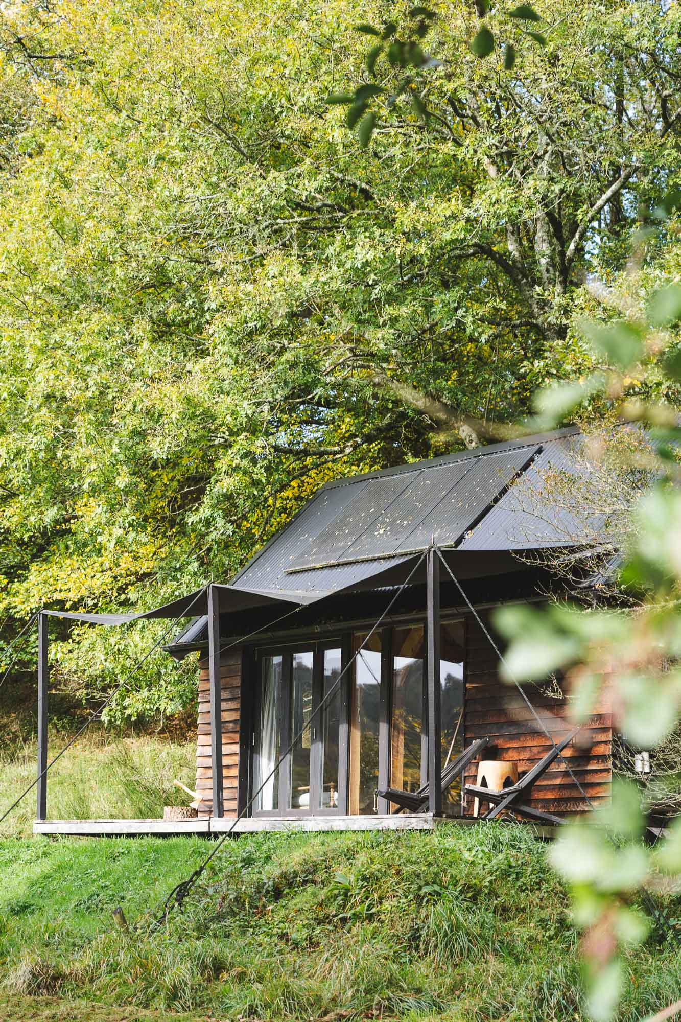 off grid wooden cabin with black cladding and canvas covered veranda, bi-fold doors overlooking landscape