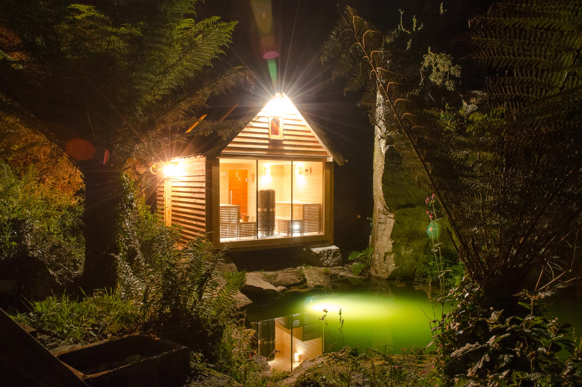 oak timber framed sauna cabin with larch cladding, copper fish scale tiles in quarry on the water with wood fired hot tub