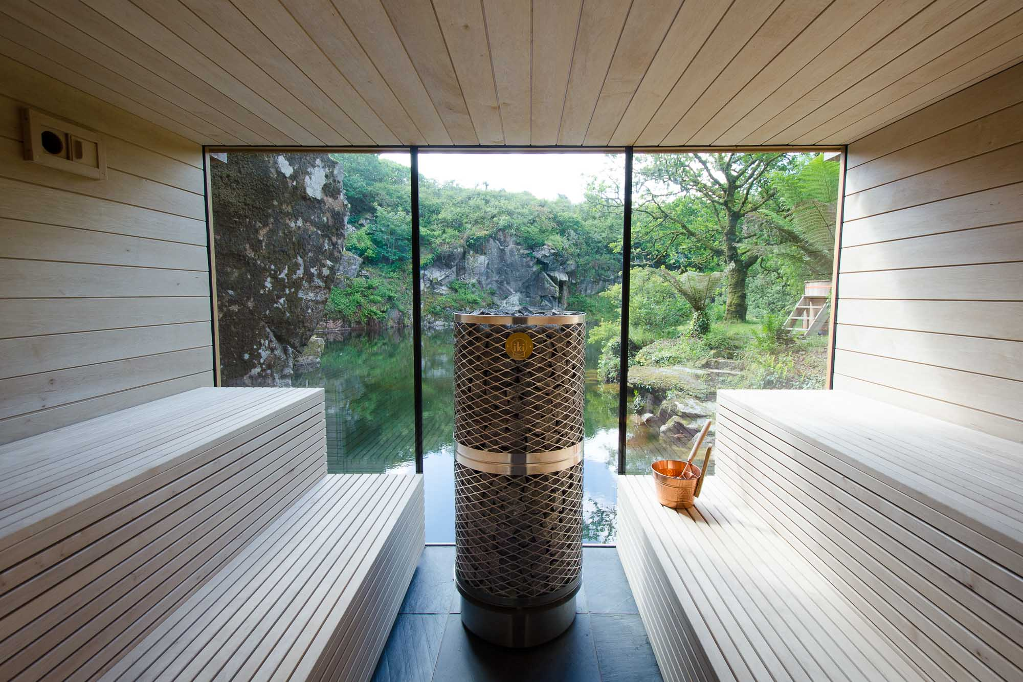 internal wooden sauna with iki sauna heater and copper bucket and ladle over looking granite quarry and water