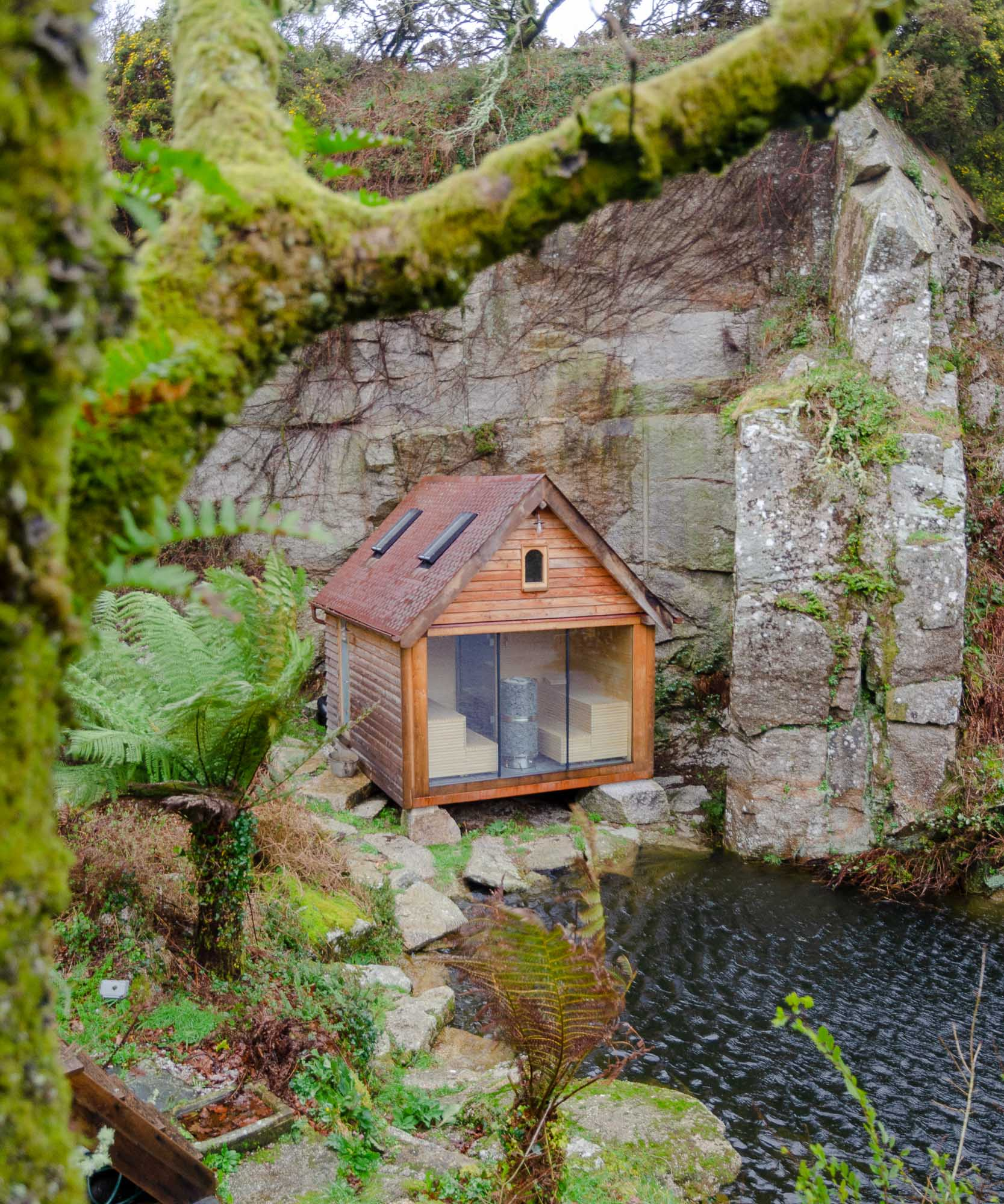oak timber framed sauna cabin with larch cladding and copper fish scale tiles in a granite quarry on the waters edge