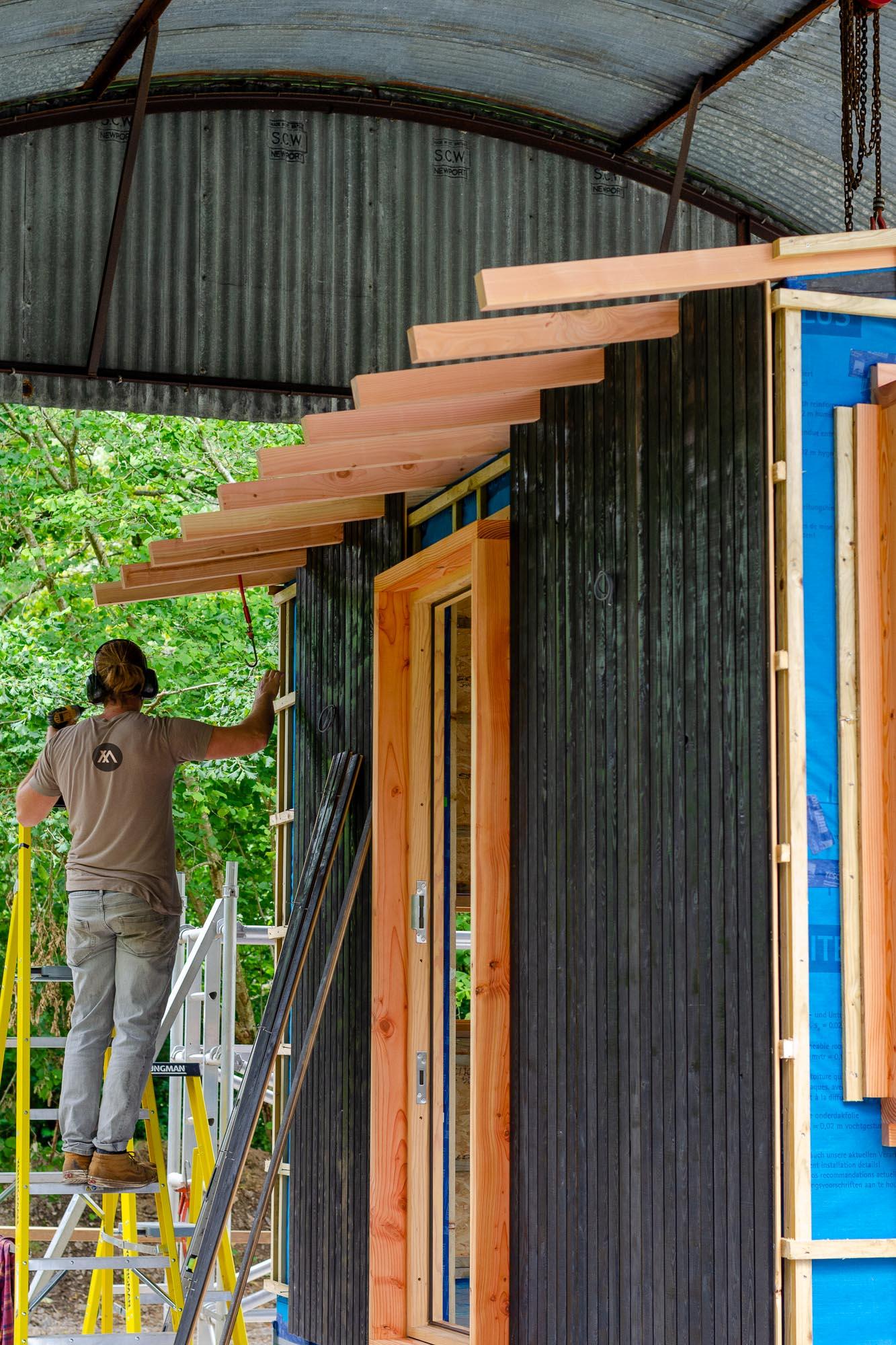 wooden nomad cabin carpenter on step ladder fixing shou sugi ban cladding