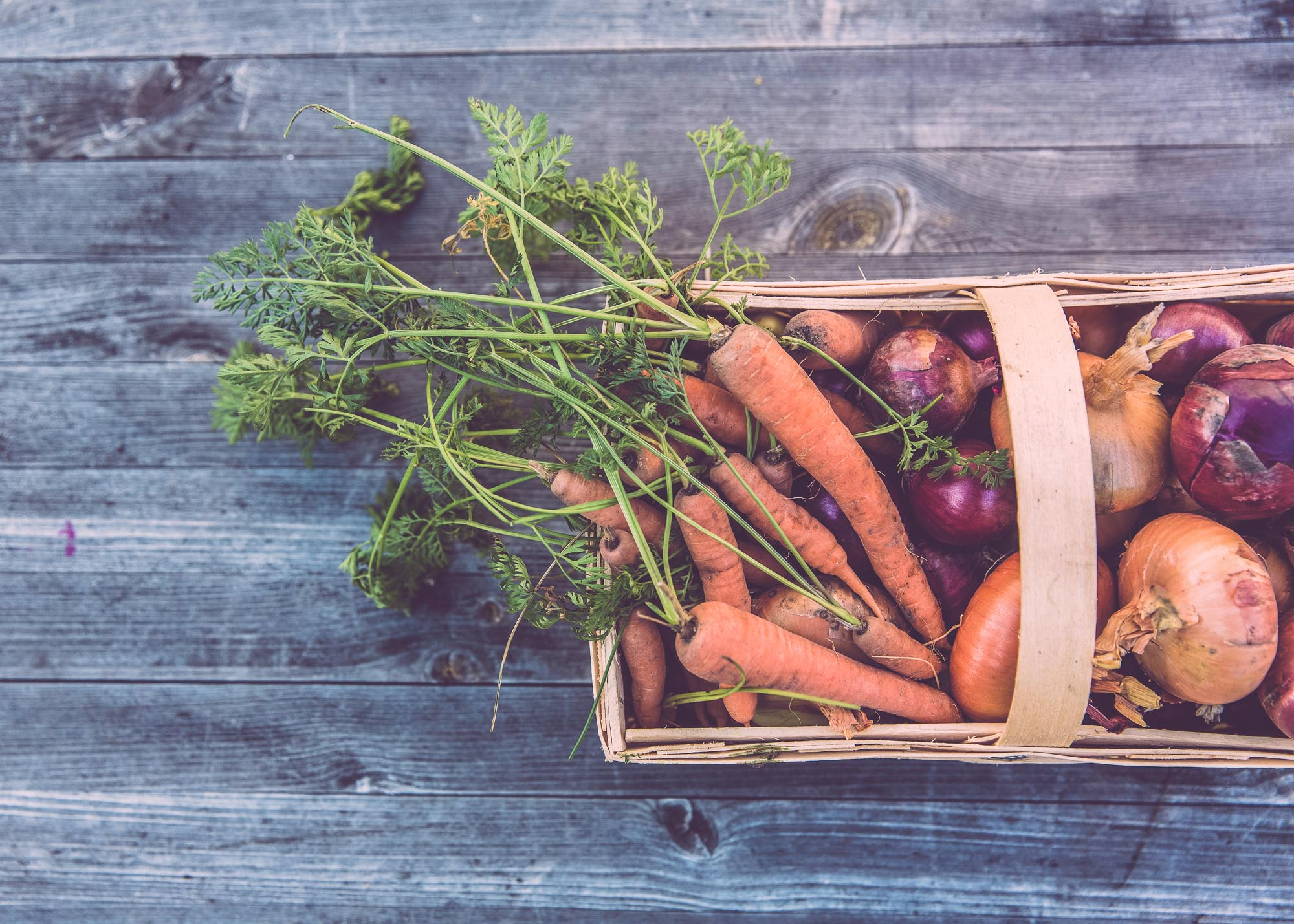 vegetable box with carrots and onions on wooden table