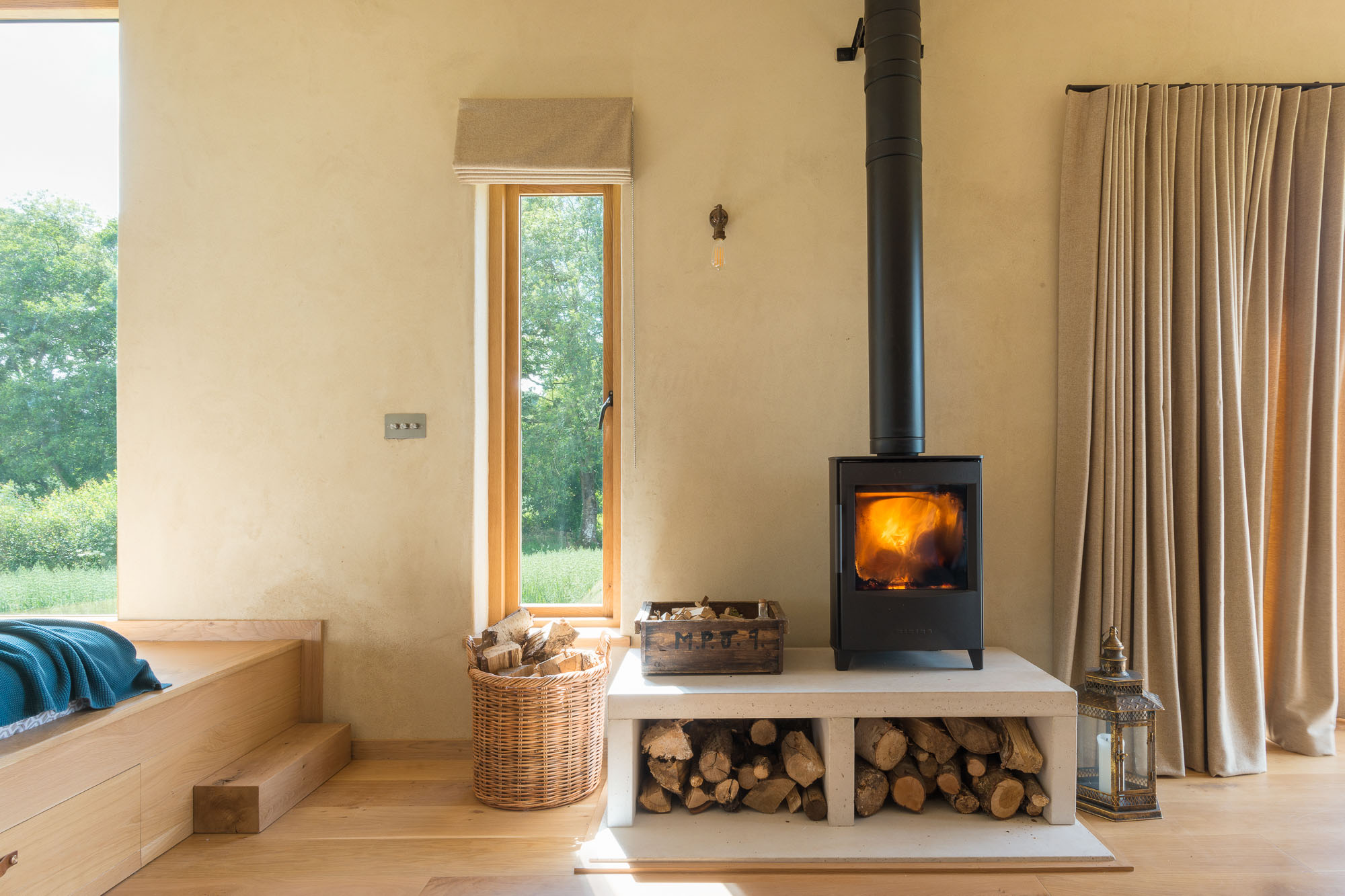 off-grid cabin interior wood burning stove, oak bed and floor, natural clay walls and windows looking over natural landscape