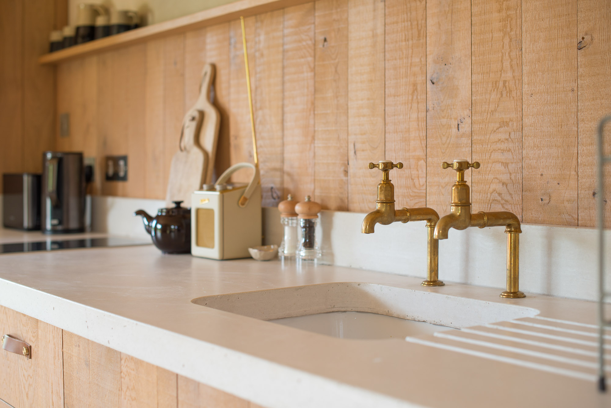 off-grid cabin interior, oak kitchen and concrete worktop, copper taps and digital radio