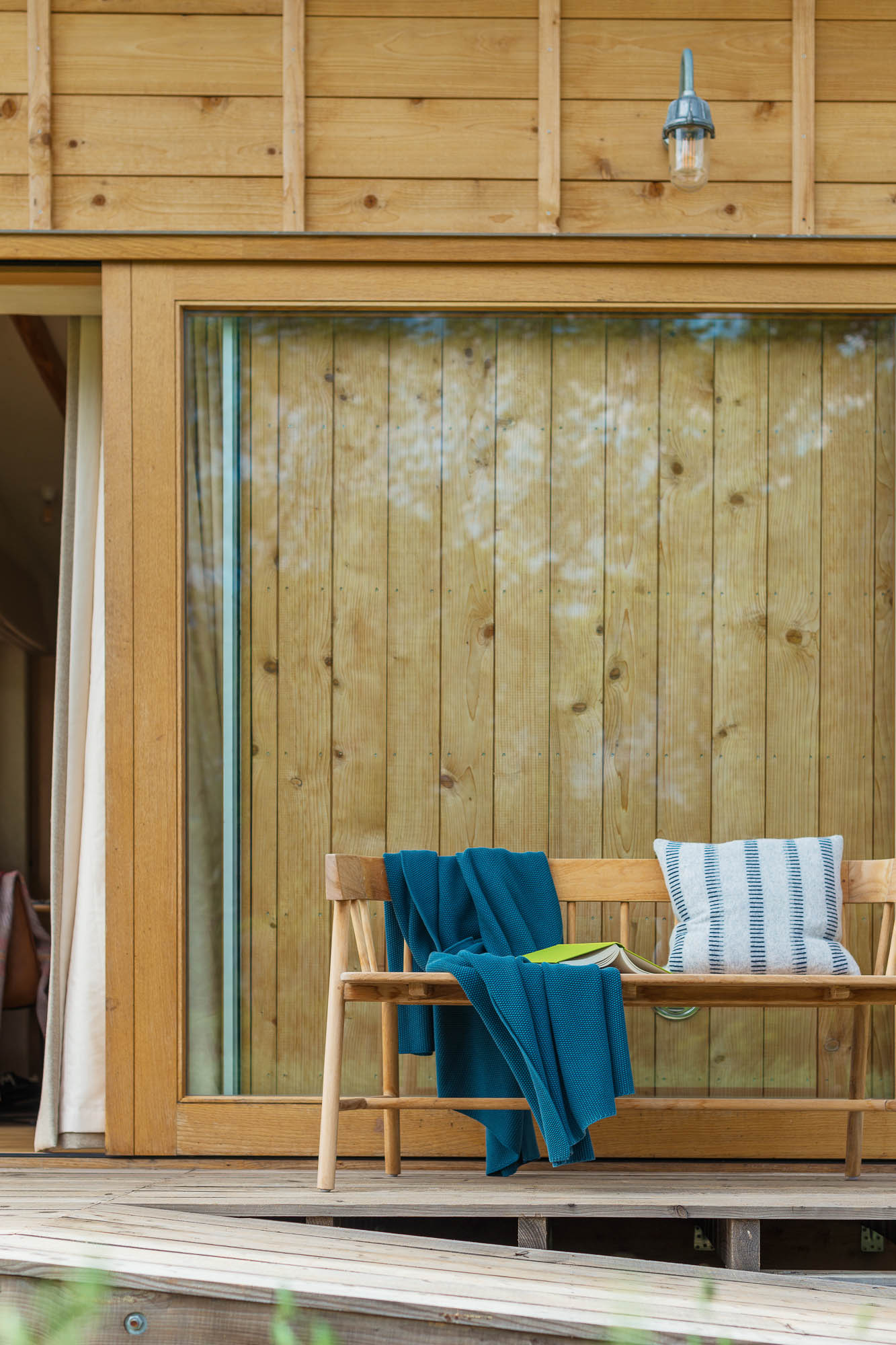 off-grid bespoke cabin exterior with outdoor seating, bench and books