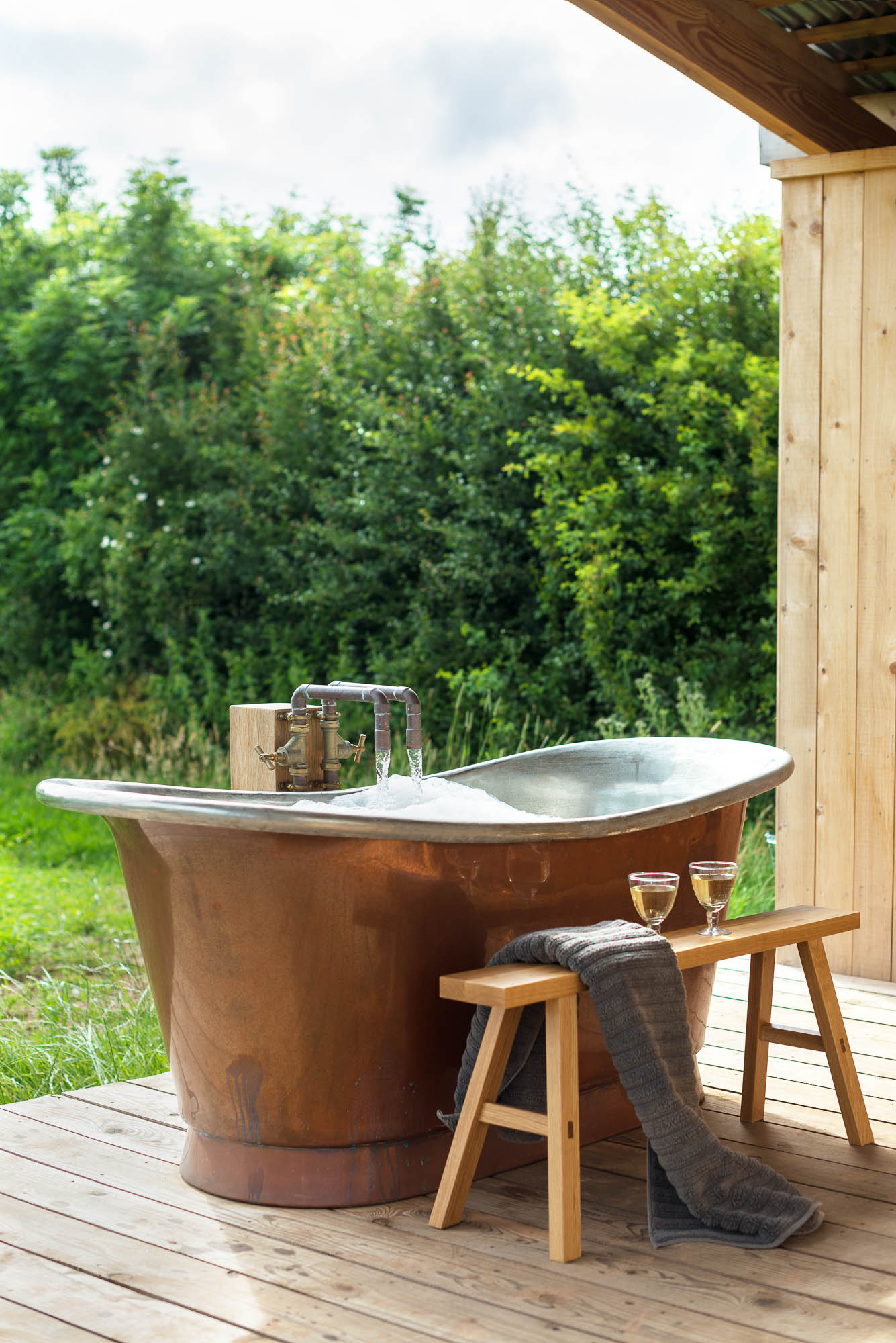 off-grid bespoke cedar cabin with covered veranda, outdoor copper bath with oak stool and champagne in the natural landscape