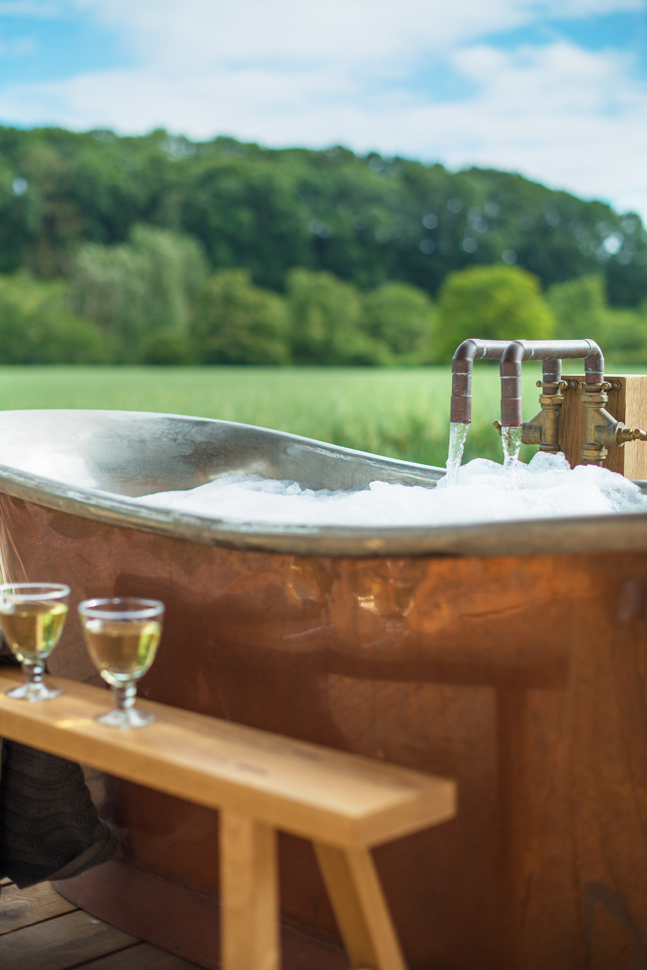 external copper bath full of hot water and bubbles overlooking fields on a sunny day