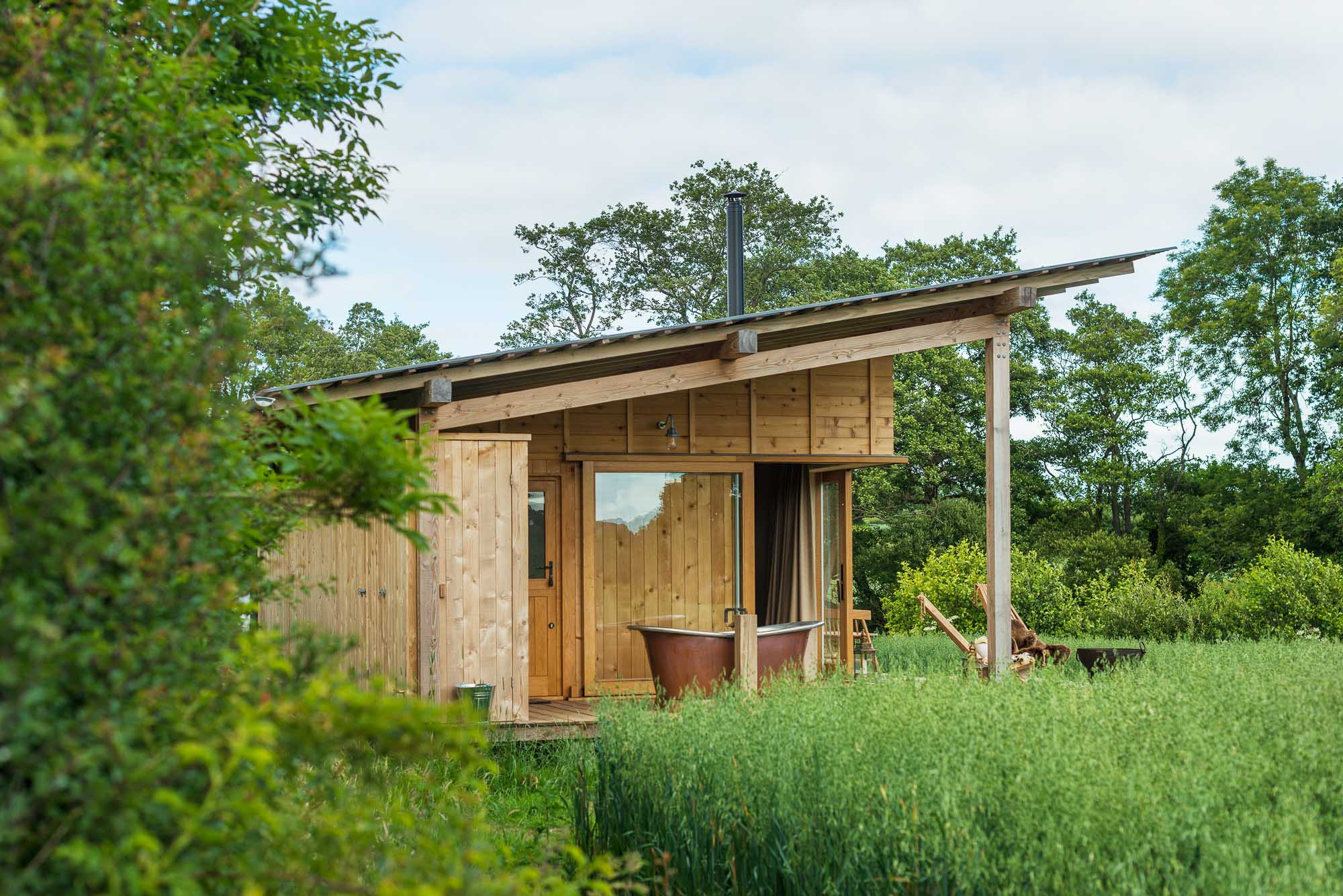 off-grid bespoke cedar cabin with covered veranda, outdoor copper bath in the natural landscape