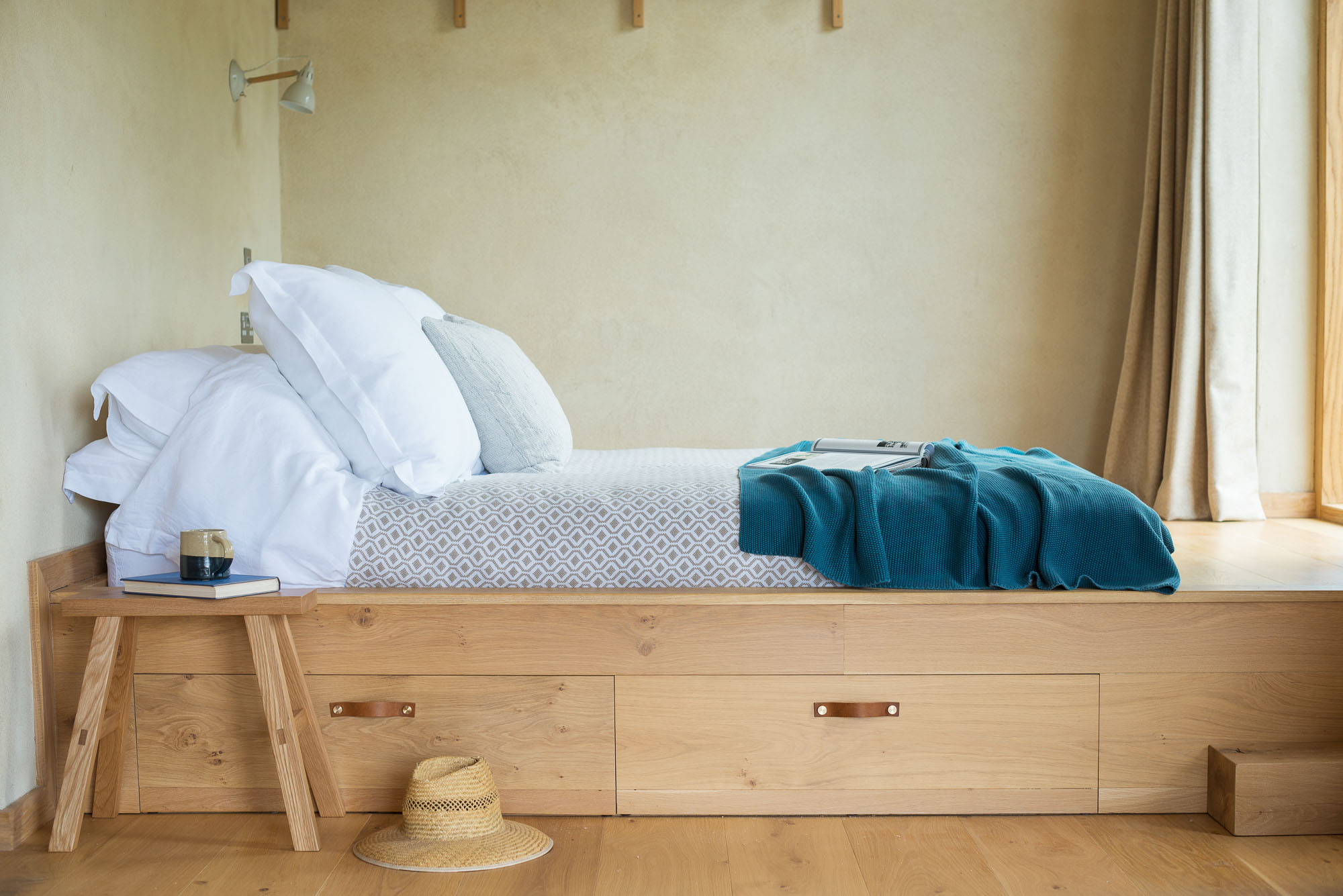 off-grid cabin interior with clay walls king sized oak double bed with leather handles, oak stool and blankets