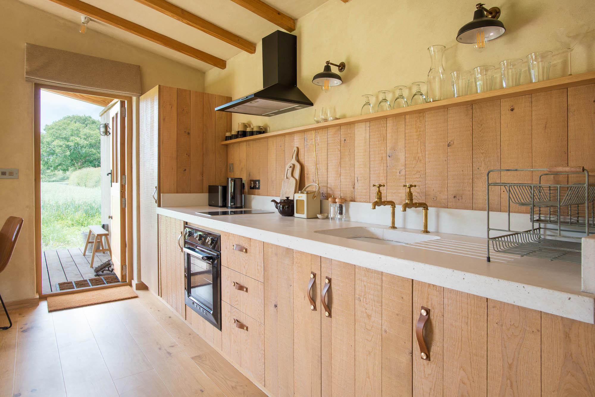off-grid cabin interior, oak kitchen and concrete worktop, copper taps and digital radio